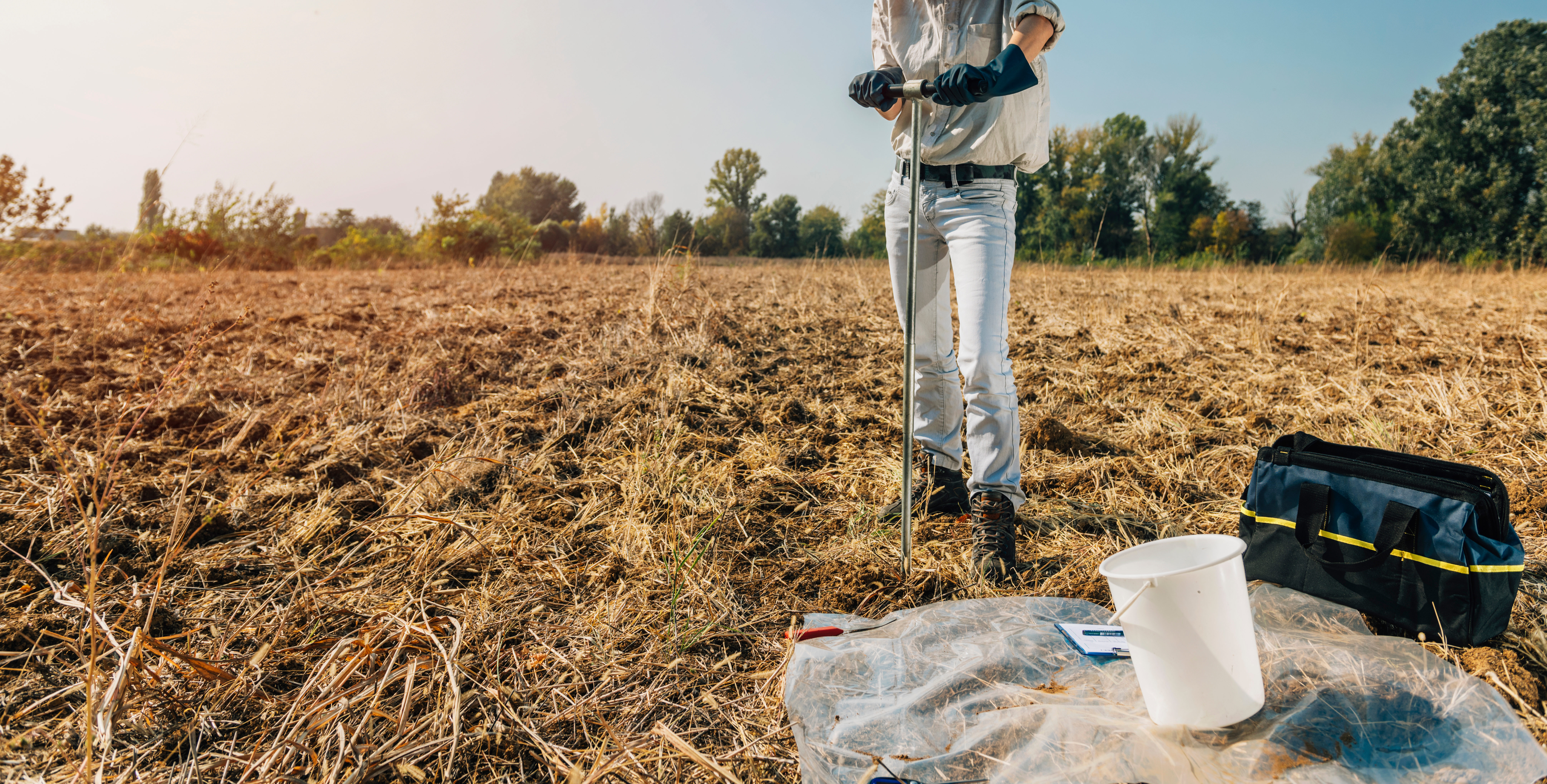 Environmental engineer in a field performing a test to assess the quality of the soil and water