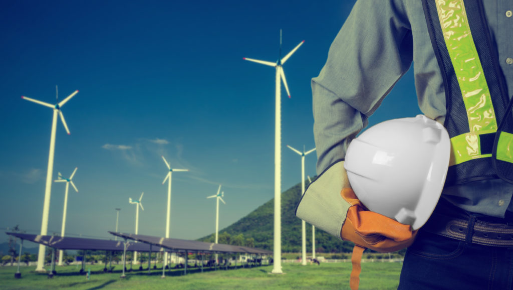 Environmental engineer standing in front of a dozen wind mills while holding his hard hat