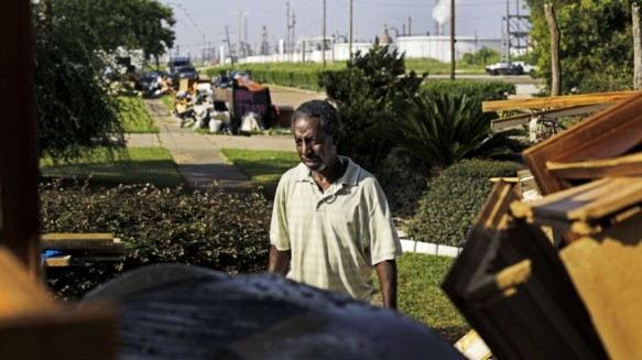 Samuel McGlory Jr., throws out debris in front of his damaged home from Hurricane Harvey as an oil refinery stands in the background