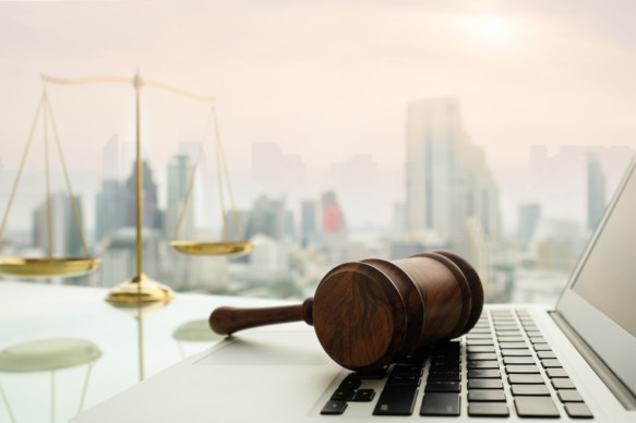 A gavel rests on top of a laptop